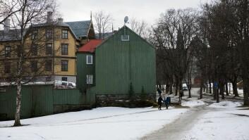 Det grønne huset i Grensen er blant dem som foreslås revet for å gjøre plass til nye universitetsbygg. I bakgrunn ses NTNUs hovedbygning på toppen av Høgskolebakken. Det gule huset til venstre i bildet er den fredede Thingvalla-gården, som etter all sannsynlighet får stå.