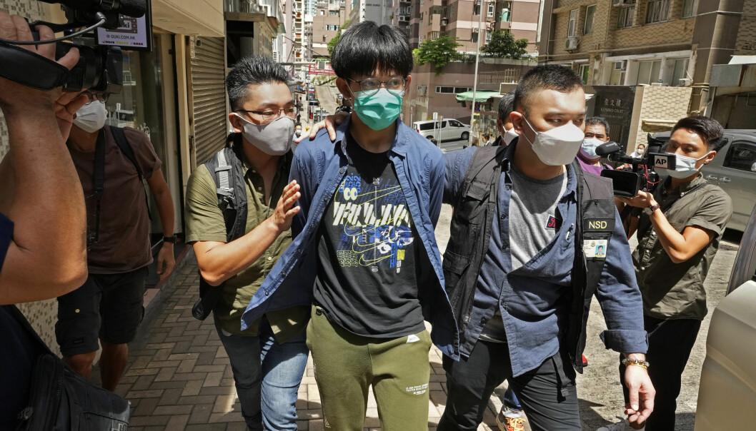 En student ved Hong Kong University (med grønn maske) blir eskortert av politiet etter arrestasjon onsdag 18. august. Til sammen fire studentledere er arrestert denne dagen.